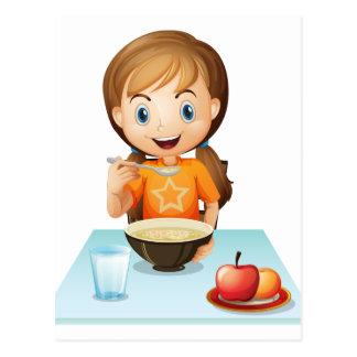 Un chica sonriente que come su desayuno tarjeta postal