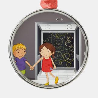 Un chica y un muchacho que llevan a cabo las manos adorno navideño redondo de metal