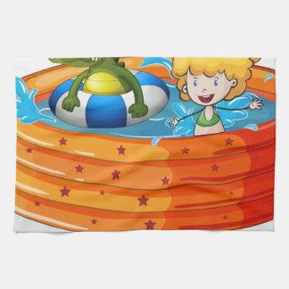 Un chica y una natación del cocodrilo dentro del toalla