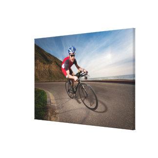 Un ciclista que se inclina en una esquina lona envuelta para galerías
