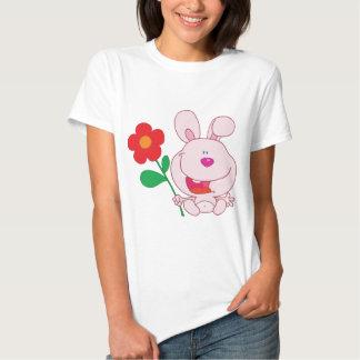 Un conejito rosado feliz sostiene la flor remeras