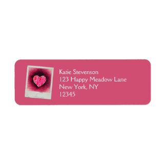 Un corazón rosado dibujado mano linda en una etiqueta de remite