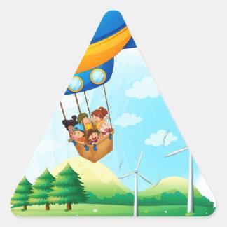 Un dirigible con los niños que pasan sobre una pegatina de triangulo personalizadas