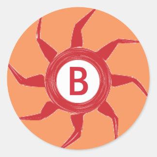 Un diseño rojo de Sun en un fondo anaranjado Pegatina Redonda