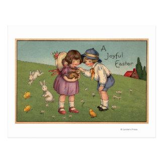 Un EasterKids alegre que sostiene un conejito Tarjetas Postales