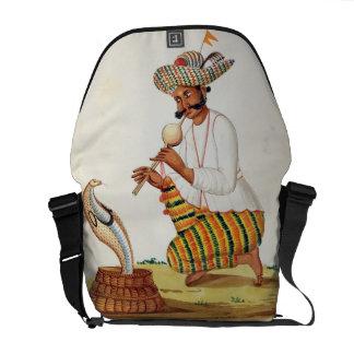 Un encantador de serpiente indio con una cobra de bolsas de mensajeria
