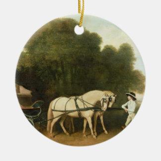 Un faetón con un par de potros poner crema en el adorno navideño redondo de cerámica