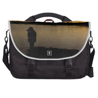 Un fotógrafo en el trabajo durante puesta del sol bolsas de portátil