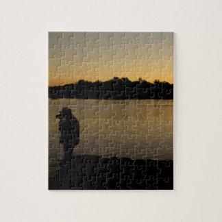 Un fotógrafo en el trabajo durante puesta del sol rompecabeza con fotos