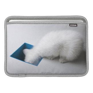Un gatito joven estira su cabeza abajo de un cuadr funda para macbook air
