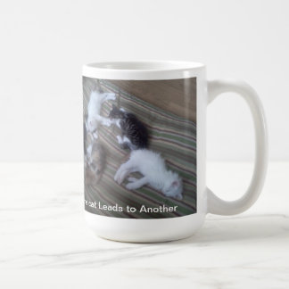 Un gato lleva a otra taza