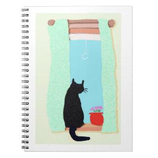 Un gato negro en el travesaño de la ventana libretas