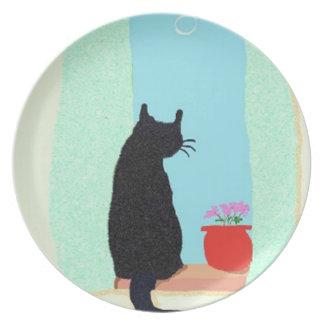 Un gato negro en el travesaño de la ventana platos para fiestas