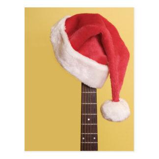 Un gorra de Santa cuelga en una guitarra acústica Postales
