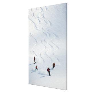 Un grupo de esquiadores backcountry sigue su guía impresiones en lona