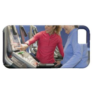 Un instructor personal ayuda a una mujer mayor en funda para iPhone 5 tough