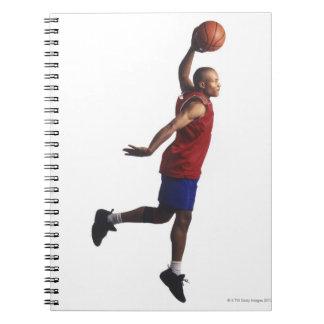 un jugador de básquet joven del varón adulto vuela notebook