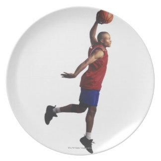 un jugador de básquet joven del varón adulto vuela plato de cena