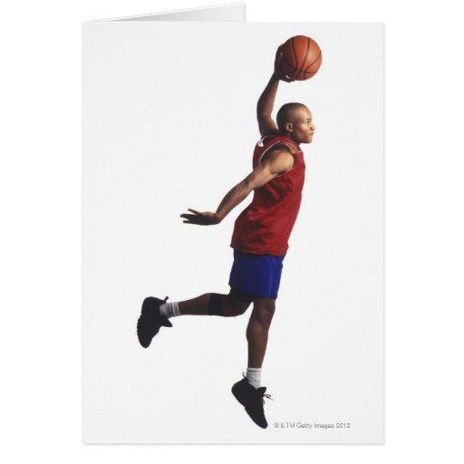 un jugador de básquet joven del varón adulto vuela tarjeta