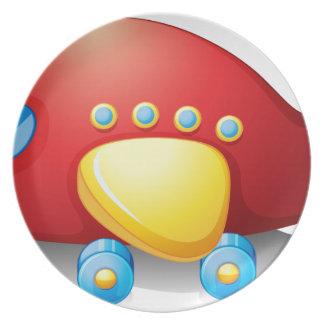 Un juguete rojo del aeroplano platos