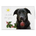 Un labrador retriever negro que trae el regalo tarjeta de felicitación