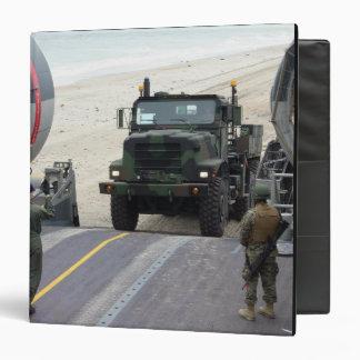 Un loadmaster dirige a un infante de marina camión