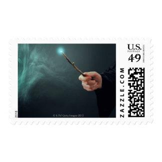 Un mago de la fantasía que hace magia con la vara sellos postales