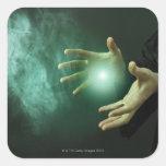 Un mago de la fantasía que hace magia con sus mano calcomanias cuadradas