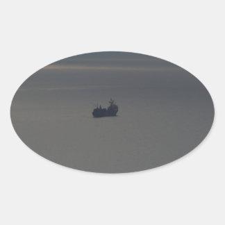 Un mar nublado y un sol poniente pegatina ovalada