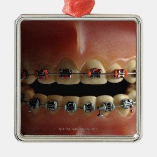 Un modelo dental y apoyos de los dientes adorno navideño cuadrado de metal