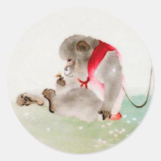 Un mono asentado observando un insecto pegatina redonda