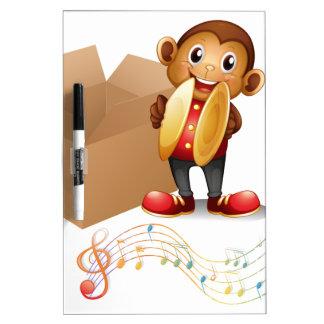 Un mono con los platillos al lado de una caja con tablero blanco