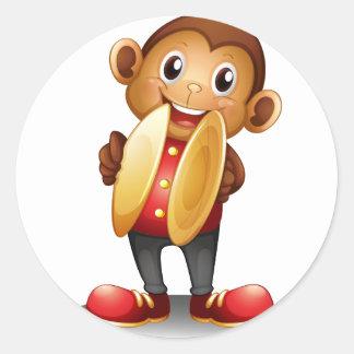 Un mono que sostiene los platillos pegatina redonda
