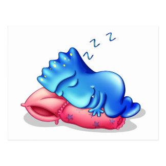 Un monstruo azul que duerme sobre una almohada postales