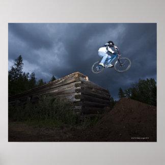 Un motorista de la montaña salta de una cabaña de poster
