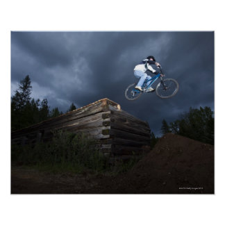 Un motorista de la montaña salta de una cabaña de  póster