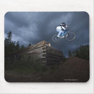 Un motorista de la montaña salta de una cabaña de  tapetes de ratón