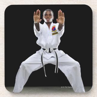 Un muchacho (15 años) en un uniforme del karate posavasos