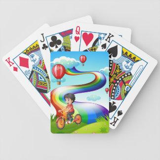 Un muchacho biking en la cumbre con un arco iris cartas de juego