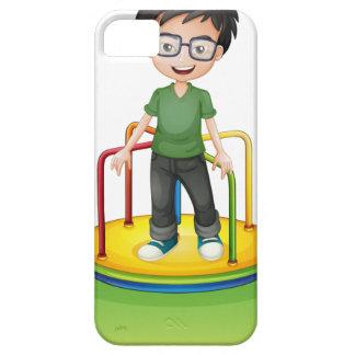 Un muchacho feliz sobre un paseo redondo colorido iPhone 5 funda