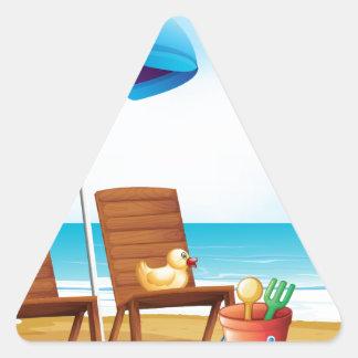 Un muchacho joven en la playa cerca de las sillas pegatina triangular