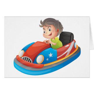 Un muchacho joven que monta un coche de tarjeta de felicitación