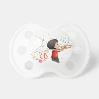Un muchacho joven talentoso que juega con la chupetes para bebés