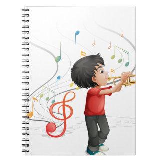 Un muchacho joven talentoso que juega con la cuaderno