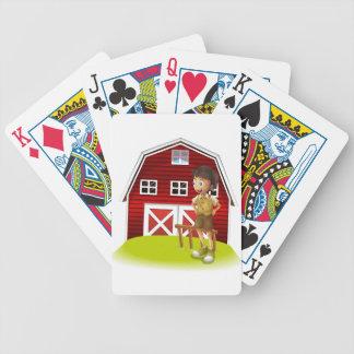 Un muchacho que se coloca delante del barnhouse baraja de cartas