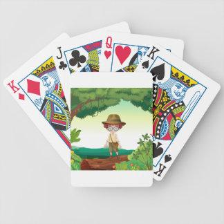 Un muchacho que se coloca en un haz de la madera cartas de juego