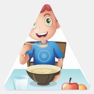 Un muchacho rizado que come su desayuno pegatina triangular
