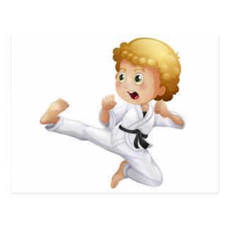 Un niño pequeño lindo que hace karate postales