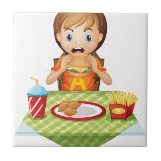 Un niño que come en un restaurante de comida azulejo cerámica