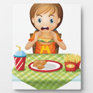 Un niño que come en un restaurante de comida placas con foto